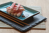 Fresh raw sushi crabsticks on plate with chopsticks