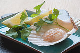 In shell fresh scallop with lemon and parsley garnish