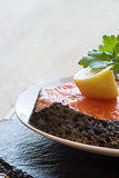 Raw fresh salmon cutlet steak with lemon and parsley garnish