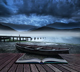 Book concept Old boat on lake of shore with misty lake and mount