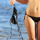 Close up of a woman on the beach in topless holding the bikini bra