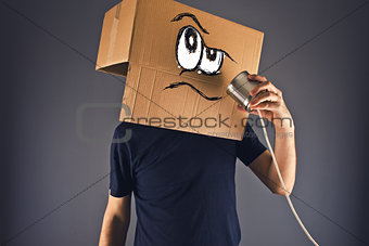 Man with cardboard box on his head using tin can telephone