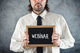 Webinar concept. Businessman holding blackboard with Webinar tit