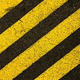 Yellow striped road markings on black asphalt.