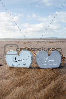 two inscribed wooden love hearts in the sand