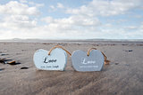 two inscribed wooden love hearts on the beach