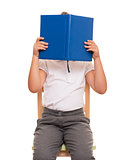 child sitting on a chair covered face with blue book