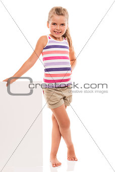 little girl is standing on white background and holding white ca