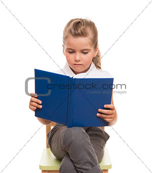 little girl sitting on a chair and reading blue book