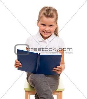 little girl sitting on a chair with blue book and smiling