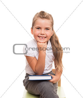 little girl sitting on a chait with book on the knee