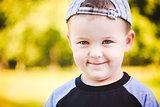 Happy Child Wearing Striped Cap In Outdoor Portrait