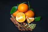 Mandarins with cinnamon, star anise and cardamom on black