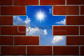 Brick wall and blue sky with clouds and sun.