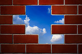 Brick wall and blue sky with clouds.