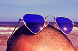man with heart-shaped sunglasses on the beach, with a retro effe
