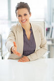 Smiling business woman stretching hand for handshake