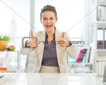 Smiling business woman showing thumbs up