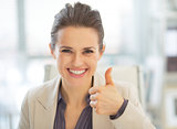 Portrait of happy business woman showing thumbs up