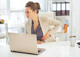 Business woman with stomach ache in office
