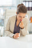 Business woman taking pill at work