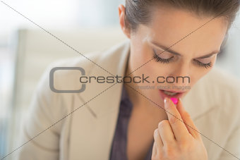 Portrait of business woman taking pill at work