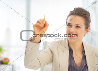 Business woman writing in air with pen