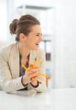 Laughing business woman holding pencils