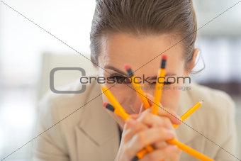 Portrait of business woman holding pencils