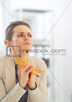 Portrait of thoughtful business woman holding pencils