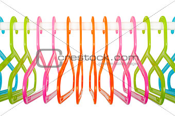Colored hangers on a rod in a wardrobe