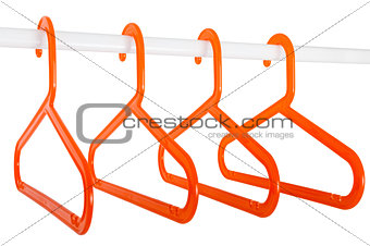 Orange hangers on a rod isolated on white