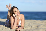 Pretty teenager girl on the phone lying on the beach