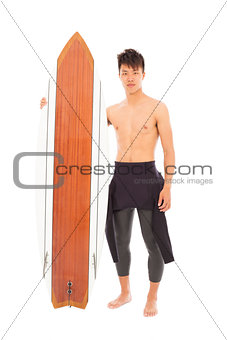 young surfer wearing diving suit and holding a surfboard