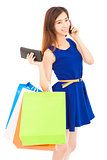 young  woman holding shopping bags and talking on the phone