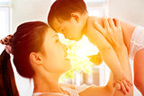 Happy  mother holding adorable child baby with sunrise backgroun