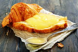 Croissant with cream and teaspoon.