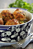 Meatballs in a blue pot on a wooden table.