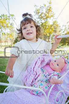 Adorable Young Baby Girl Playing with Baby Doll and Carriage