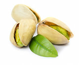 Three pistachio nuts with leaf