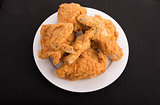 Plate of Fried Chicken on Black Background