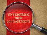 Enterprise Risk Management. Magnifying Glass on Old Paper.