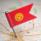 Kyrgyzstan Small Flag on a Map Background.