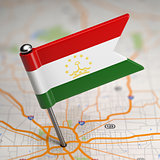 Tajikistan Small Flag on a Map Background.