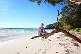 Cheerful teen boy sitting on tree  holiday at the beach Australi