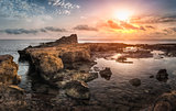 Sunset over the Sea and Rocky Coast with Ancient Ruins