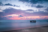 Tropical Beach with Empty Cage in the Sea at Sunset