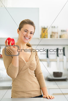 Portrait of happy young woman apple in kitchen