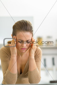 Portrait of stressed young woman in kitchen