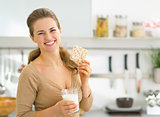 Happy young woman having snacks in kitchen